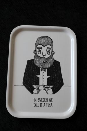 """Fikabrickan är helt klart Karin Ohlssons storsäljare som sålts i flera tusen exemplar. Mycket tack vare att Designtorget tog in den i sitt sortiment. – När jag tänkte på vad jag skulle skriva kom jag in på Sällskapsresan och när de säger """"In Sweden we call it a kick"""" och då blev det bara """"In Sweden we call it fika"""", säger Karin."""