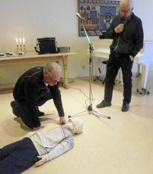 Svein Aune visar hjärt- och lungräddning med en medhavd docka. Vid mikrofonen syns Jarl Christoffersson.