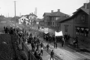 Stationsområdet som det såg ut på 1930-talet. Närmast till höger ses Järnvägshotellet, därefter stationshuset och signalverkstaden. Kortet är taget vid en 1 maj-demonstration, en stor folksamling som gick genom centrala Ljusdal.