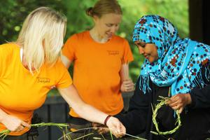 Maria Platzgummer, Madelene Krug och Rahma Adam Ibrahim lindar kransar tillsammans i   trädgården vid Träslottet i Arbrå.