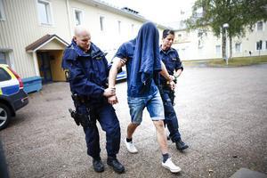 En av de häktade männen på väg till häktningsförhandlingen.