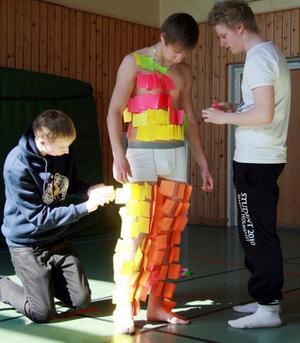 Med flinka händer fäster Daniel Olofsson och Martin Holmkvist post-It-lappar på Dennis Persson.