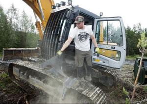 Simon Näslund städar ur sin grävmaskin innan det är dags för nästa skift att att ta över.