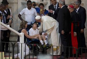 Påve Franciskus hälsar på ett rullstolsburet barn i Havanna på Kuba. På kort tid har han förändrat bilden av hurdan en påve ska vara.