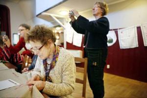 87-åriga Hilma W Danielsson från Sveg anser att brodera är ett lustfyllt skapande. Här ser vi henne brodera ett meddelande på en jättelik duk på det stora bordet. Alla deltagare på helgens workshop fick brodera på duken.
