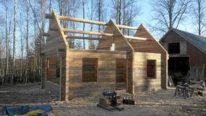 Ett timmerhus byggs på en plats och plockas sedan ner för att sättas ihop igen på den plats där huset slutligen ska stå.