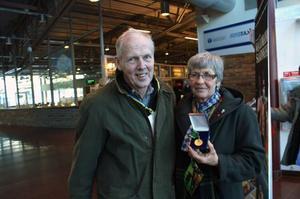 Ingvar och Anita Molander visar stolt upp sin guldmedalj som de fått för att ha levererat prickfri mjölk under 23 år. Foto: Seved  Johansson