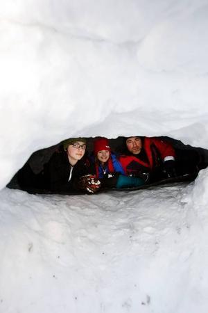 """Snögrottan som familjen byggde i Valla mäter cirka tre meter i diameter och med en cirka en meter i höjd. """"Det var rätt så kallt att sova i den"""", berättar Sara Borg Bromée. Med på bilden är brorsan Egil och pappa Johan Bromée.  Foto: Ulrika Andersson"""