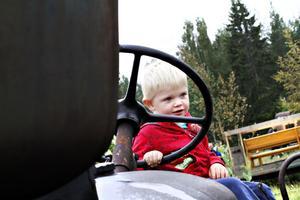 Treåriga Ludvig Eriksson från Tierp sitter på förarplatsen på en traktor som ett annat barn beskriver som