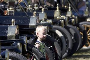 VÄNTADE 97 ÅR. Lille Adam Granlund, 3 år, från Långhundra i Knivsta föddes 97 år efter att den första T-Forden började rulla. I går försvann han nästan bland alla blänkande klenoder i Högbo.