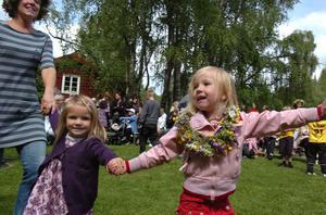 Emilia Wisserlinck och Hedda Westberg dansar runt midsommarstången.