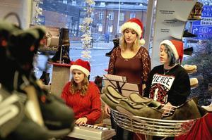 Stämningsfullt. Lilly Röök Sahlin, Madelene Andersson och Erika Anerstedt sjöng julsånger inne på Oscaria. Utanför skyltfönstret lyste 120 marschaller upp gatorna.  Foto: Adam Söder