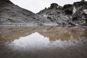 På Kattvikskajen täcks snöhögarna av sand och omringas av vatten.
