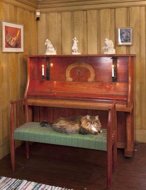 Pianot och pianostolen är delar av ett rödbetsat möblemang som ritades för storstugan i Norhaga.