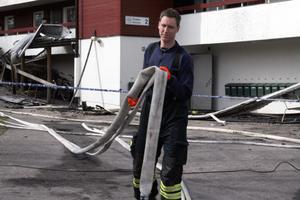 Jakob Lindsmyr i full färd med att samla ihop vattenslangarna. När Jakob natten mellan fredag och lördag kom till hyreshuset var det en fullt utvecklad brand. Hela taket brann då, berättar han.