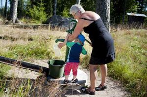Carin Gisslén-Schönning hämtar vatten för att blanda saft åt barnbarnet Benjamin Heyman-Schönning.