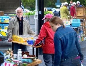 Bordsflytt. Det började regna när försäljarna just höll på att packa upp sina saker. Rolf och Maria Andersson såg till att få sina saker under tak.