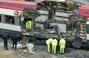 Spanish railway workers and police examine the debris of a destroyed train at Madrid's Atocha railway station, Friday, March 12, 2004. Powerful explosions rocked three Madrid stations on Thursday, March 11, 2004, killing more than 190 rush-hour commuters and wounding more than 1,240 in Spain's worst terrorist attack ever. (AP Photo/Anja Niedringhaus)