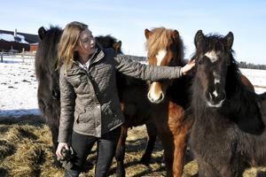 Mailinn Solér i en av gårdens hästhagar, tillsammans med några av gårdens islandshästar.