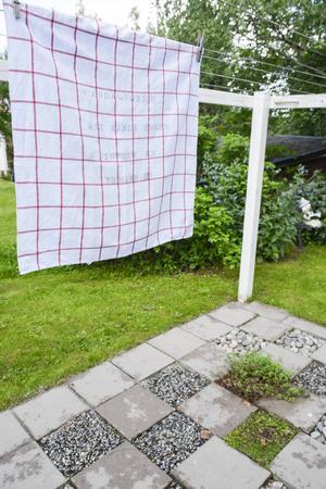 Under den hemmasnickrade tvättställningen ligger ett rutmönster av plattor och växter. Som man kan läsa på handduken så får den som hänger tvätt njuta av väldoft från Salvia under arbetet.