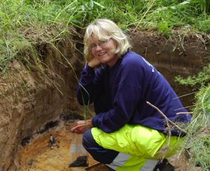 Kolprov. Eva Carlsson kryper ner i en av de djupaste groparna för att spara en del av kolet i marken för eventuell testning senare. Förutom kolrester hittades inget av större intresse under onsdagens utgrävningar. Foto:Dan Havemose