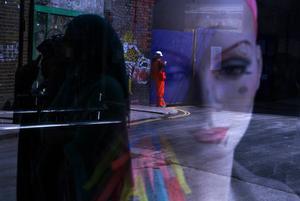 Speglingar av två kvinnor som går förbi och en byggnadsarbetare som lutar sig mot byggnaden i bakgrunden syns i skyltfönstret med skyltdockans ansikte. Bilden är från Brick Lane.