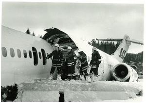 Brandmän från Rimbos räddningstjänst i arbete på den sargade flygplanskroppen.