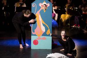 De andra cirkusartisterna lurar Emma att sätta sitt ansikte på en rosa panter.