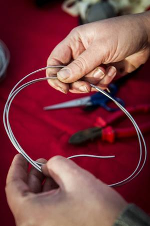 Böj till en rund ring av ståltråd. Tråden ska lindas ihop några var så att ringen blir stabil.