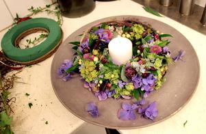För bordet. Hortensia, krysantemum, stjärnflocka och hyperikumbär i oasis runt ett ljus.