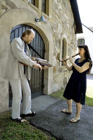 Pehr Falkenström spelar nyckelharpa och Hélèn Nevers crumhorn framför kyrkan i Viby.