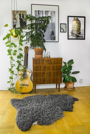 Byrån är köpt second hand och gitarren har Lina Lindbladh fått av sin mamma. Tavlorna är blandade loppisfynd. Tavlan med skogsmotiv är från Grandpa och den med husmotivet är från Fotografiska. Ullmattan kommer från en gård på Gotland.