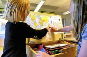 Världsvana nallen Simon. Isa Linder hittade en världskarta i en papperskorg och förbarmade sig över den. Nu kan både hon och klasskamraten Alina Skarp peka ut var Simon varit och var de hoppas att han kommer att färdas, Australien bland annat.Foto: Sofia Gustafsson