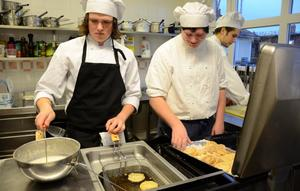 Full fart i köket. Isak Winkvist och André Aronsson ser till att struvorna doppas i frityrolja och sockras. Bakom jobbar Jonathan Cehlin med julgodiset.
