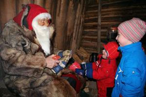 Alva överlämnar sin julklapp till tomtefar. Gammeltomten satt i kolarkojan och tog emot önskelistor och hade inte räknat med att han själv skulle få en julklapp.Fem musiktomtar spelade durspel i storstugan. Här ser vi två av dem