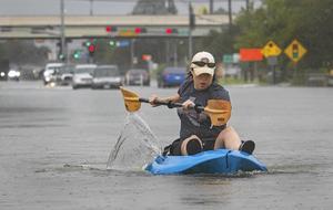 En kvinna paddlar för att ta sig fram på en gata i Texas som översvämmats av ovädret Harvey.