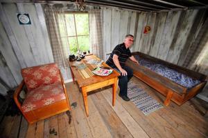 Hembygdföreningens ordförande Christer Birgersson visar upp kojan där Lars Theodor Jonsson bodde. Kojan finns numera på hembygdsgården i Strömsund. Den är fortfarande sotskadad efter en brand.