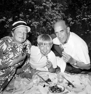 Picnic i det gröna. En finklädd familj njuter av en vacker sommardag på 50-talet.