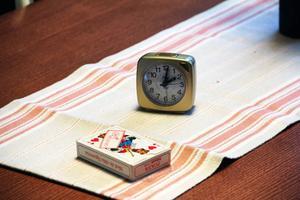 Vid det enkla bordet mitt i rummet står några stolar. På bordet står en väckarklocka och ligger en kortlek. Båda är symboler på väntan.