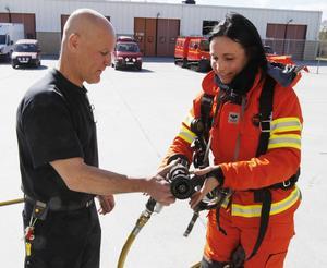 Brandmannen Lars Askrud på räddningskåren i Östersund visar Ilona hur munstycket fungerar.