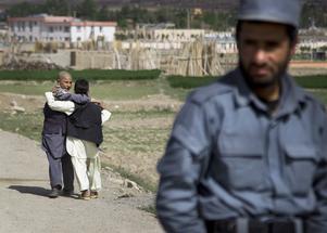 Två pojkar passerar en poliskontroll efter en väg som leder till Narkhdistriktet i Wardak-provinsen, Afghanistan. Bilden är från 2013.