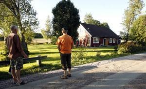 tappade släpet. Johnny Karlsson och vännen Hans Lindström begrundar eländet. Det var uppe vid grusvägen som traktorn tappades släpet och hjulspåren i gräsmattan visar hur det for nedför slänten rakt in i husväggen.