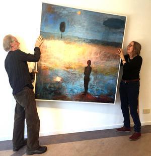 Lars och Ingela Agger hjälps åt att hänga upp tavlor inför utställningen på Galleri K.