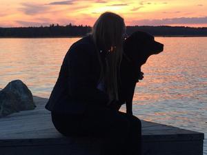 En stämningsfull bild som visar riktig kärlek mellan Lillmatte Sara och labradoren Stårsa när de sitter på sin egen brygga i solnedgången med Ridön i bakgrunden. Stårsa väljer Sara före att bada i vattnet.