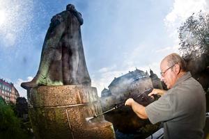 Thomas Berglund drar på högtrycket och spolar bort mossa och alger som lagrats under nästan ett hundra år på Karl XIV Johan.