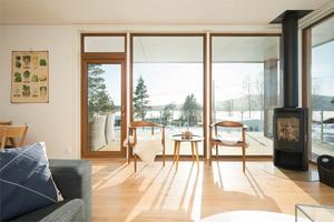 Stora fönster från golv till tak mellan vardagsrum och altan.