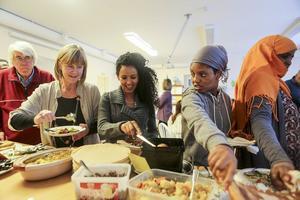 Gunilla Lagercrantz (tv) tar för sig av det internationella smörgåsbordet tillsammans med några av eleverna på kommunens lärcentrum för vuxna.