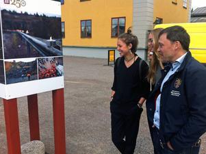 Falu rödfärg står bakom en ny fotoutställning vid Falu gruva. Lugneteleverna Emilia Arnell och Maja Tekla Jonsson, som levererat bilder till utställningen från fjolårets jubileumskonsert, visar Johan Molin, vd, sina alster.