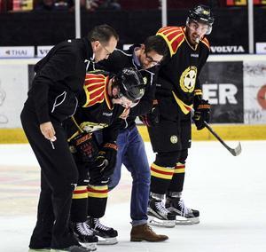 Brynäs massör Pär Thures och läkare Henrik Wrethling hjälper Petr Vrana av isen. Marc Zanetti tittar också till sin lagkompis.