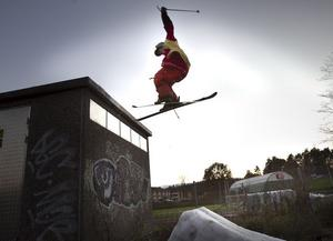 Pelle Axelsson tar sats på taket, snurrar runt och landar i högen med spillsnö nedanför.
